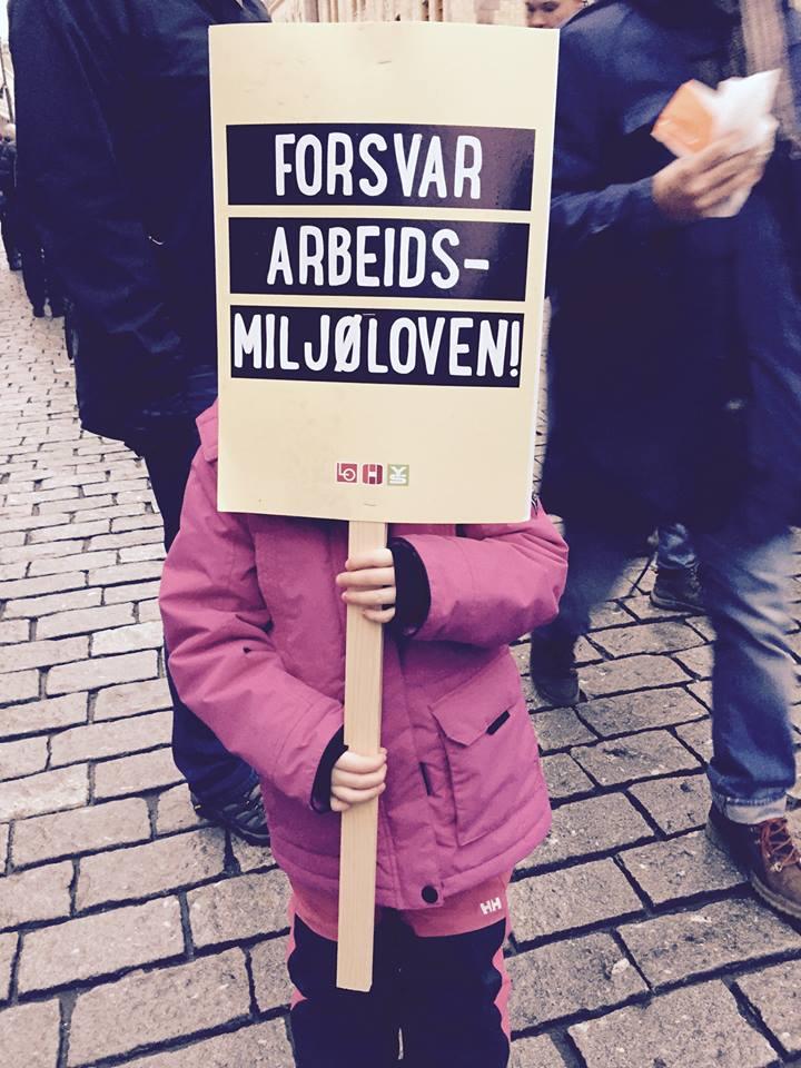 Bilde av jente som holder skilt med forsvar arbeidsmiljøloven