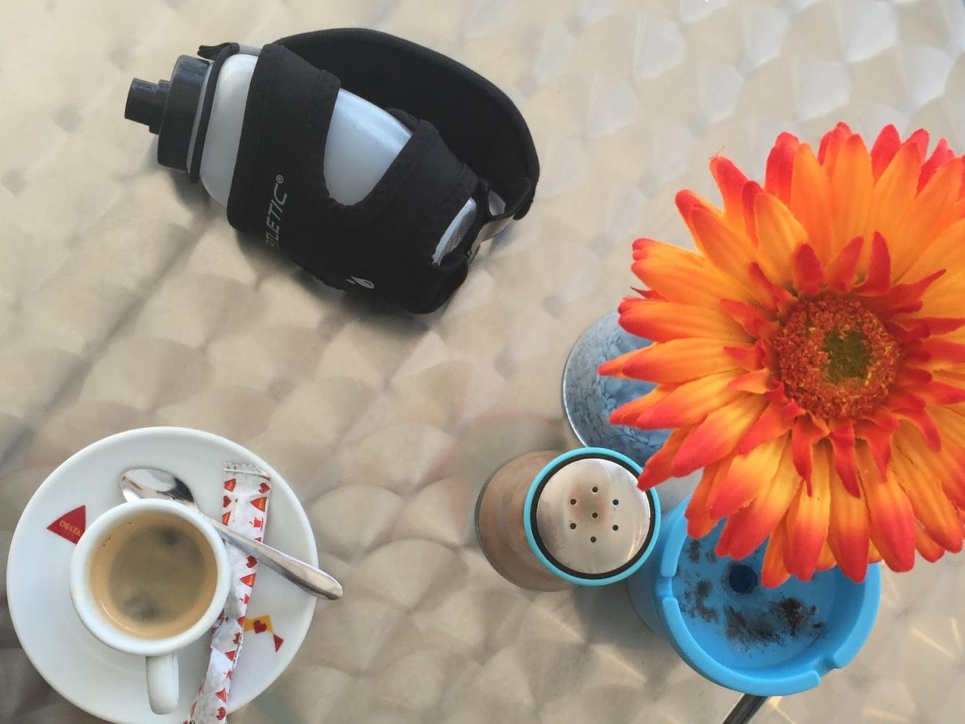 Bilde av blomst, kaffe og løpeflaske