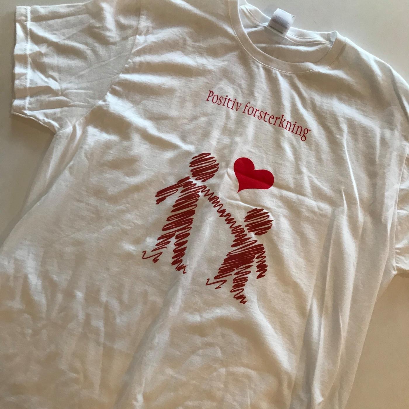 Bilde av t-skjorte med teksten «Positiv forsterkning» og to mennesker som holder hverandre i hånden.